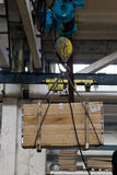 Crane lifting a box. The crane in a warehouse lifting a box Stock Images