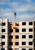 Crane lifting cement block on background of building under construction Royalty Free Stock Photo