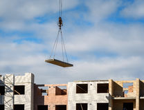 Crane lifting cement block on background of building under construction Royalty Free Stock Photos