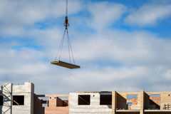 Crane lifting cement block on background of building under construction Stock Photos