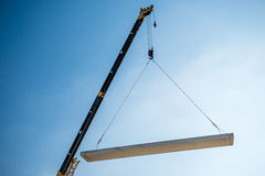 Crane lifting cement block Royalty Free Stock Images