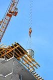 Crane lifting cement mixing container Royalty Free Stock Photos
