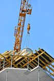 Crane lifting cement mixing container Royalty Free Stock Images