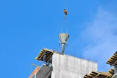 Crane lifting cement mixing container Royalty Free Stock Image