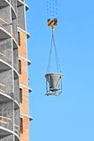 Crane lifting cement mixing container Royalty Free Stock Photography