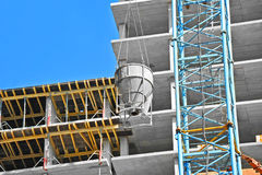 Crane lifting cement mixing container Stock Image