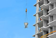 Crane lifting cement mixing container Royalty Free Stock Photo