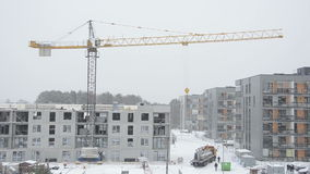 Crane lifting concrete block house part and workers in snowstorm stock video