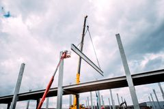 Crane lifting concrete frameworks, shutterings and heavy prefabricated concrete components at construction site stock photography