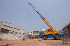 Crane lifting concrete mixer container at construction site Stock Photos