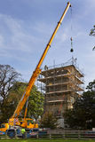 Crane Lifting Masonary - Church Roof Restoration. A crane lifting restored masonry up to restoration craftsmen on the tower roof of an old parish church in the Stock Photos