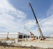 Crane lifting metal beam Stock Image