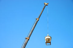Crane lifting mixed concrete container. Against blue sky at construction site Stock Image