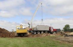 Crane lifting septic tanks Royalty Free Stock Images
