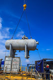 Crane lifting storage tank Stock Image