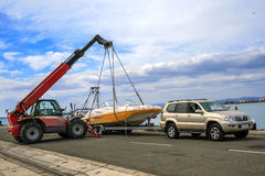 Crane lifts a boat. Recreational boat being lifted by heavy industrial crane machinery against blue sky background Stock Photo