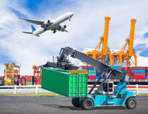Crane lifts a container to commercial delivery cargo container. Truck in an industrial harbor and cargo plane flying above ship port for logistic import export royalty free stock photography