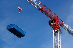 Crane lifts a dumpster. Construction site crane is lifting truck dumpster on the blue sky Royalty Free Stock Photo