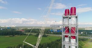 The crane lifts metall segment of a large chimney pipe system. Aerial shot