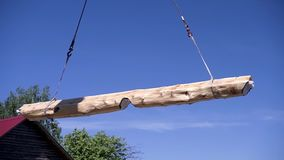 Crane lifts timber on construction site. Clip. Construction process with lifting of heavy beams by means of crane. Crane. Lifts treated log on sky background stock video footage