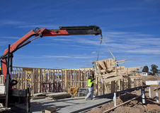 Crane lifts trusses onto new houses under construction. Workman guides trusses being lifted by crane at new housing estate Stock Photo