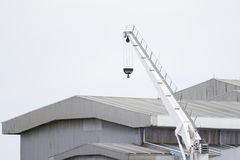 Crane lifts the white with a factory background. Royalty Free Stock Image