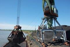 Crane loading coal to ship at Kolyma river port Royalty Free Stock Photos
