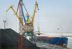 Crane loading coal to ship Royalty Free Stock Photo