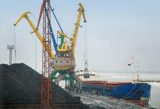 Crane loading coal to ship Royalty Free Stock Photo