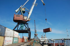 Crane loading metal container to ship at Kolyma river port Royalty Free Stock Photo