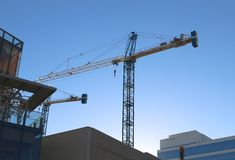 A Crane Loading Plywood Onto a Building Royalty Free Stock Photos
