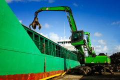 Crane loading a ship with recycling steel. In industrial docks Royalty Free Stock Photos