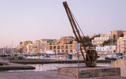 Crane and loading zone, in Kalkara Bay with waterfront, harbour and skyline stock image