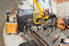 Crane loads garbage into truck at construction site Royalty Free Stock Image