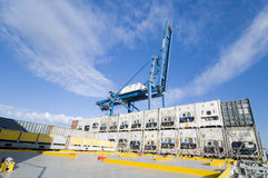 Crane lowering container to stack of containers. Royalty Free Stock Images