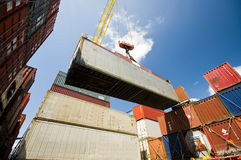 Crane lowering container to stack of containers. Stock Photography