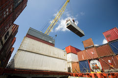 Crane lowering container to stack of containers. Royalty Free Stock Photography