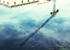Crane is mirroring in water, retro photo filter Royalty Free Stock Images