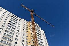 Crane and modern building against blue sky. Royalty Free Stock Photo