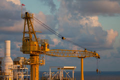 Crane na planta de petróleo e gás a pouca distância do mar para o elevador pesado do apoio e transfira alguma carga os outros luga Fotos de Stock Royalty Free