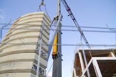Crane near building on blue sky Stock Photos