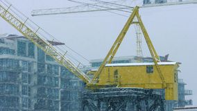 Crane Near Buildings In Heavy Snowfall stock footage