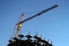 The crane and new building. The elevating crane on construction of a new building Royalty Free Stock Image