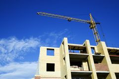 The crane and new building. The elevating crane on construction of a new building Royalty Free Stock Photography