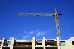 The crane and new building. The elevating crane on construction of a new building Stock Photo