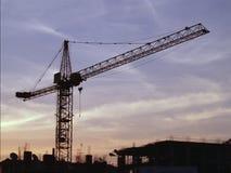 Crane on a newly built residential multi-storey house against blue sky, white lightning, sunrise. Stock Photography