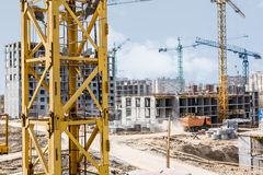 Crane next to a building under construction. Buildings under construction with cranes against the blue sky. Colorful construction cranes in Ukraine Stock Images