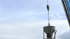Crane o cascalho das descargas da cubeta em um silo em uma planta concreta filme
