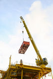 Crane operation transfer cargo on the platform and moving cargo from supply boat, heavy lift in oil and gas construction platform.  royalty free stock photos
