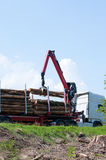 Crane operator loading logs on to truck Royalty Free Stock Photos